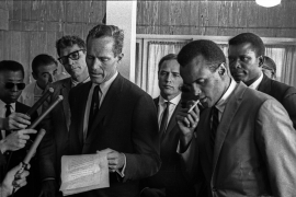 Charlton Heston reading a civil rights declaration on behalf of the Hollywood delegation. Left to right: James Baldwin, Burt Lancaster, Marlon Brando, Harry Belafonte and Sidney Poitier. Washington National Airport, DC. August 28, 1963