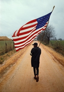 "Selma to Montgomery March 1965 Day 4, Will Henry ""Do-Right"" Rogers with his hand-made flag and home-made pole, on the Rogert Gardner Farm Road, Lowndes County, 23 March 1965. Call for pricing."