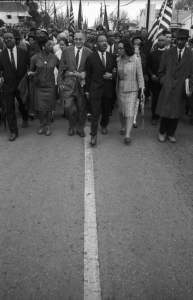 Selma to Montgomery March 1965 Day 5, Triumphant civil rights leaders entering Montgomery on Oak Street. From left to right: Ralph and Juanita Abernathy, Ralph Bunche, Dr. Martin Luther King, Jr. and Coretta Scott King with Frederick Reese. Price on request.