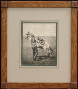Andy Spellman Saddling the Wild Horse, Ekalaka, Montana 1894Collotype, size 10 x 8 inchesFrame: 21 x 18 inchesArts & Craft style, quarter sawn oak frame with buffalo skull logo in corners. Archival framing materials with hand applied French lines. Price: $1550.00